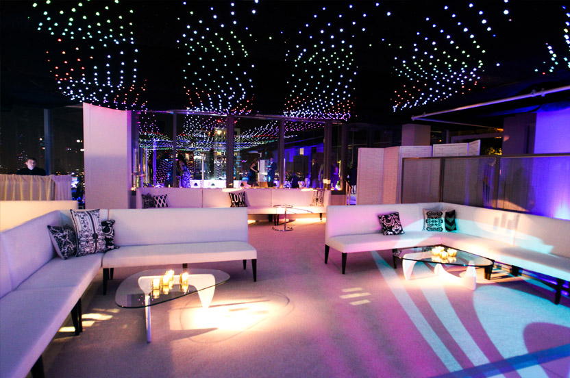 The super white cocktail space was transformed with lighting and a lot of furniture re-arranging.  We also tore off 8,000 square feet of white stretch ceiling to reveal this computer-controlled light screen.