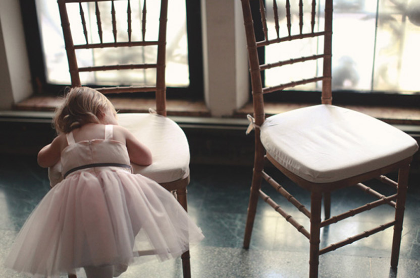 A tired flower girl makes for a sweet photo opportunity while waiting for the ceremony to begin.