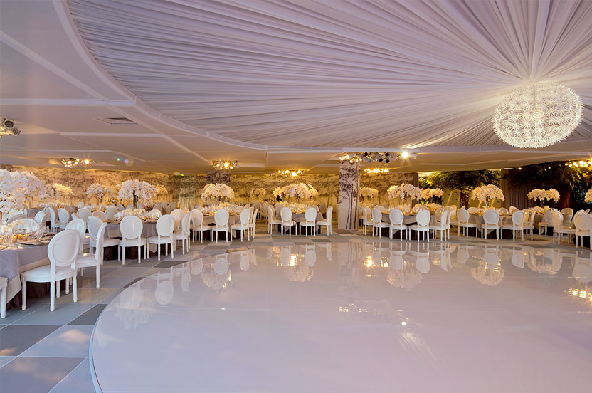Walking into the ballroom, guests are greeted with a truly contemporary garden in the sky. A surrounding scrim of forest trees, acres of orchids and a dandelion puff chandelier provide focus. The 180-degree skyline provides a breathtaking backdrop to the band. The dance floor is white Lucite, in an oval mirroring the ceiling treatment.