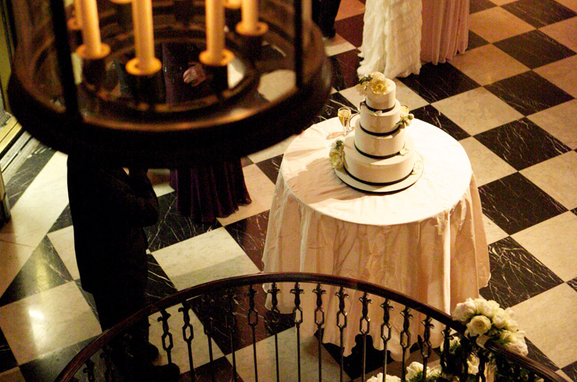 The stunning cake has white sugar peonies and the wedding's black ribbon ties made in fondant on every layer.