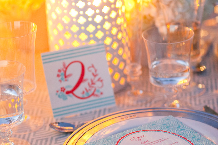 Table numbers are propped up by pierced lanterns that glow beautifully when lit.