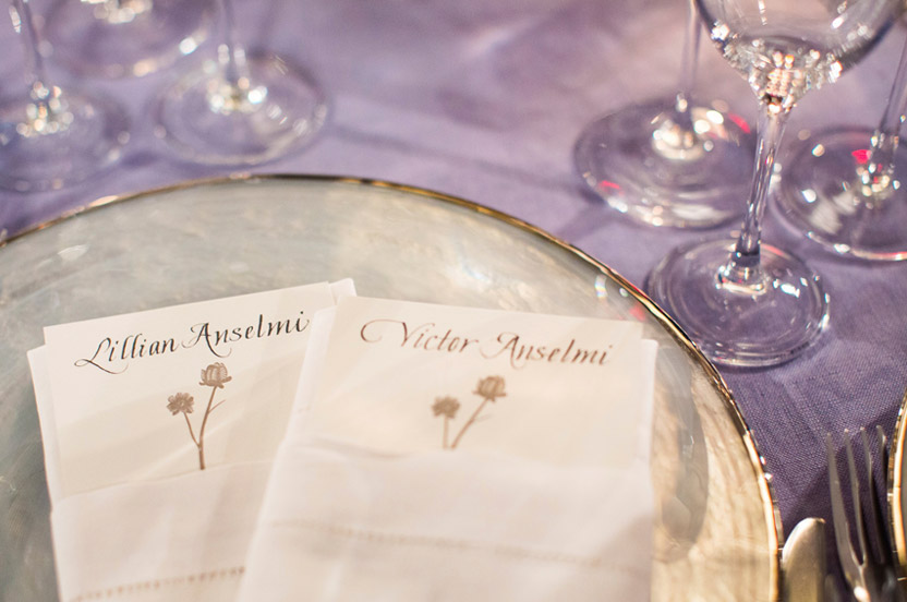Wedding Library chargers show off the lovely linens and hand-lettered menu place cards.