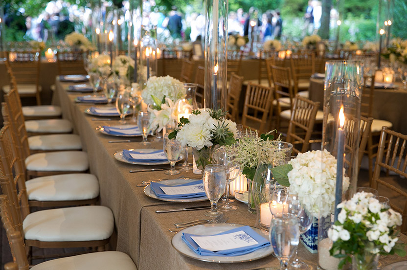 We often added a natural craft background instead of stark white when possible to further elevate the look. Creamy white flowers and chair cushions and sailor-blue tapers and napkins tie the look together.