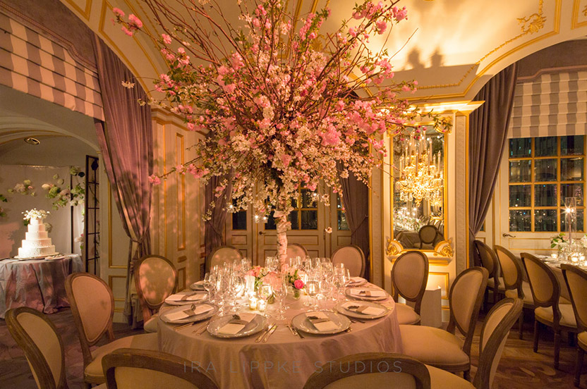 "Round tables in the corners created the opportunity for tall, towering tree arrangements that appear to magically grow from the center of the tables. The arrangements ""anchor"" the room and lend a dramatic yet peaceful symmetry."