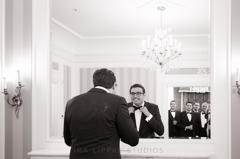 The groom applies some finishing touches to his wedding ensemble, while his groomsmen and father look on.