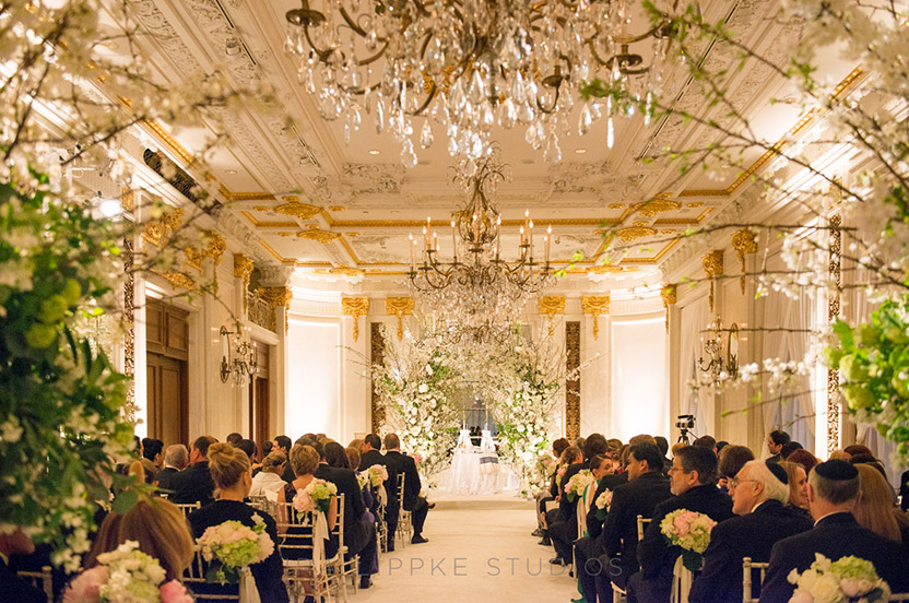 Key design elements include laying white carpet over the busy patterned one, hanging ethereal white drapes, introducing pure white lighting, garden-white ceremony chairs and an explosion of white flowers and flowering branches for the huppah.