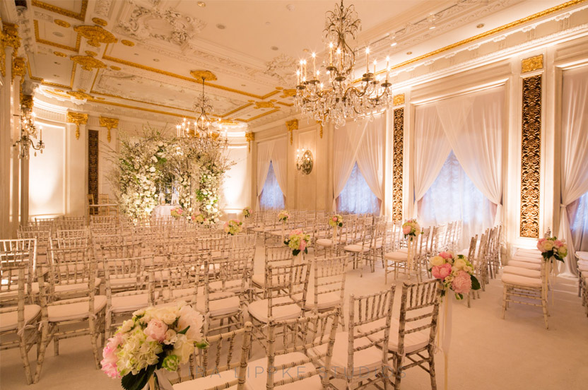 The Versailles Ballroom is transformed from its regal Louis XVI crimson and gold style to a dreamy, wedding-perfect ceremony backdrop.