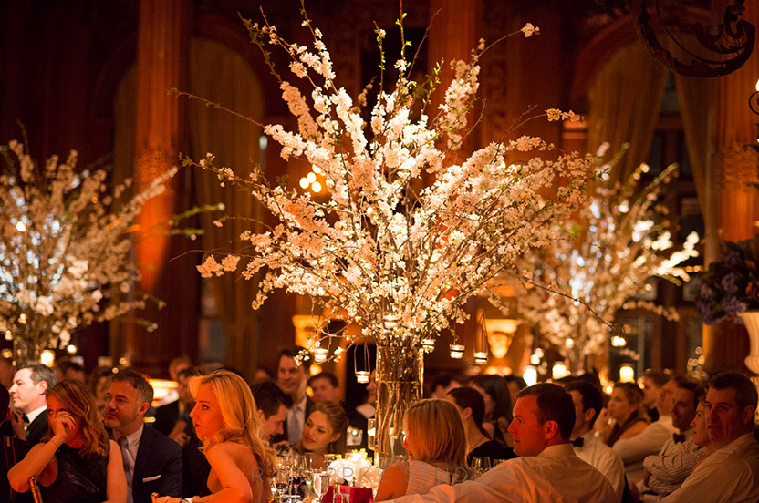One of the best parts of springtime weddings is the ability to utilize flowering branches. Alternating tables with white cherry blossoms add height to the party and help fill the vast room.